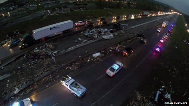 A still from aerial drone footage shows emergency vehicles and debris on a highway south of Mayflower, Arkansas