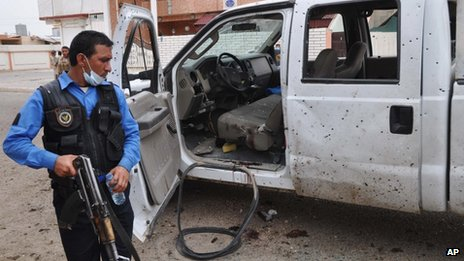 An Iraqi policeman inspects the site of a suicide attack at a polling centre in Kirkuk, Iraq, 28 April 2014