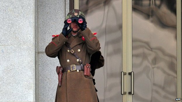 A North Korean soldier looks on at the South side at the truce village of Panmunjom in the Demilitarised Zone dividing the two Koreas on 12 March 2014