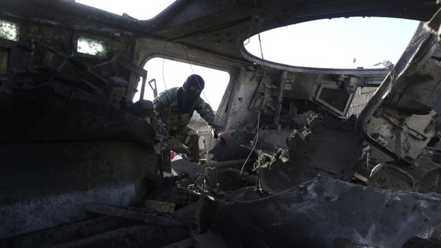 A member of the military personnel inspects a damaged army vehicle after a suicide bombing at an army camp in Benghazi, 29 April 2014