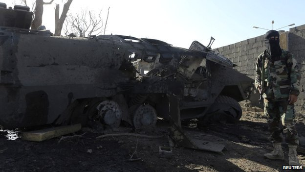 A member of the military personnel stands next to a damaged army vehicle after a suicide bombing at an army camp in Benghazi, 29 April 2014