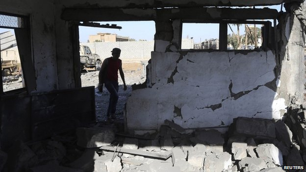 A member of the military personnel inspects the damaged guard room after a suicide bombing at an army camp in Benghazi, 29 April 2014