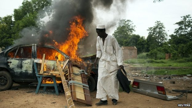 A man stands near a vehicle and other belongings set on fire by its owners who did not want to leave them behind for looters in Bangui, Car (27 April 2014)
