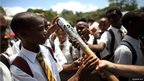 Students from Dominica Grammar School reach in to touch the Queen's Baton in Roseau, Dominica.
