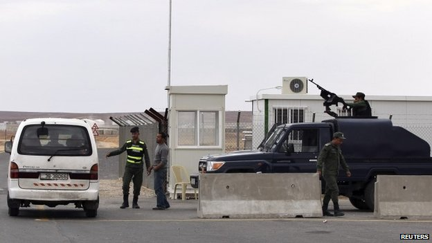 Police officers stand guard at the entrance to Azraq camp
