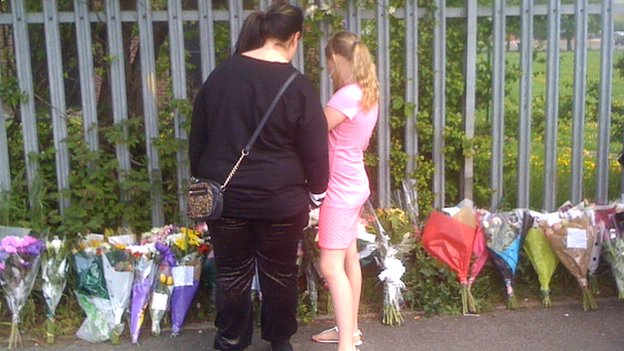 People looking at floral tributes