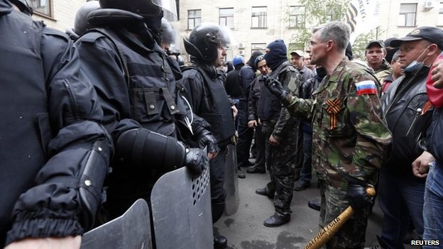 Pro-Russian activists confront interior ministry security personnel outside the regional government's headquarters in Luhansk (29 April 2014)