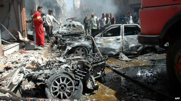Emergency personnel and civilians inspect the site following a car bomb explosion in the Abbasiyah neighbourhood of Syria's central city of Homs, 29 April 2014
