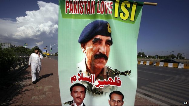 "A man walks past a banner showing a picture of Pakistan""s Inter-Services Intelligence Chief Lt. General Zaheerul Islam, center, displayed by traders to show their support for the Pakistani army and ISI, in Islamabad, Pakistan, Saturday, April 26, 2014."