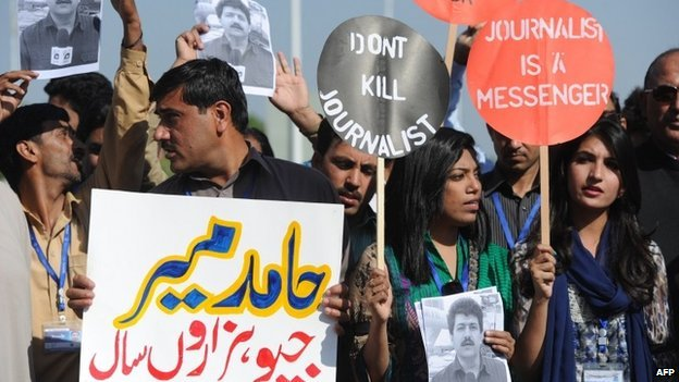 Pakistani journalists hold placards and photographs bearing the image of Geo television journalist Hamid Mir during a protest against the attack on Mir by gunmen in Islamabad on April 23, 2014.