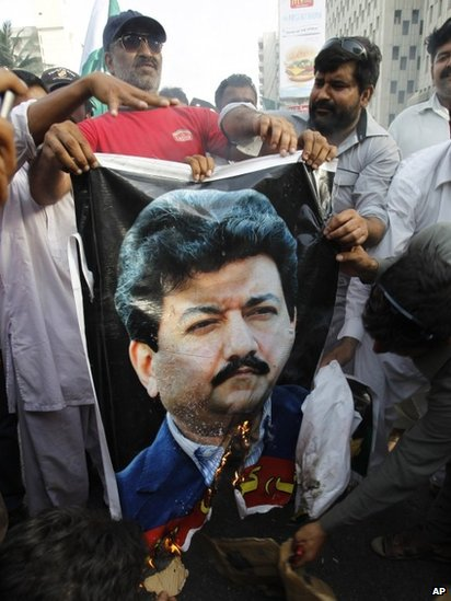 Supporters of the Pakistan army burn a poster of Pakistani anchorperson Hamid Mir at a rally in Karachi, Pakistan (26 April 2014 photo)
