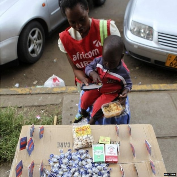 Thulisa Sibanda feeds her son as she waits for clients to buy mobile phone cards in central Harare, April 1, 2014.