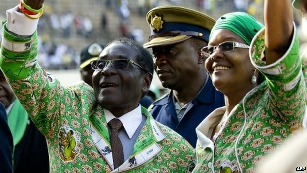 President Robert Mugabe (2nd L) greets supporters alongside his wife Grace Mugabe after his address at a rally in Harare on 28 July 2013
