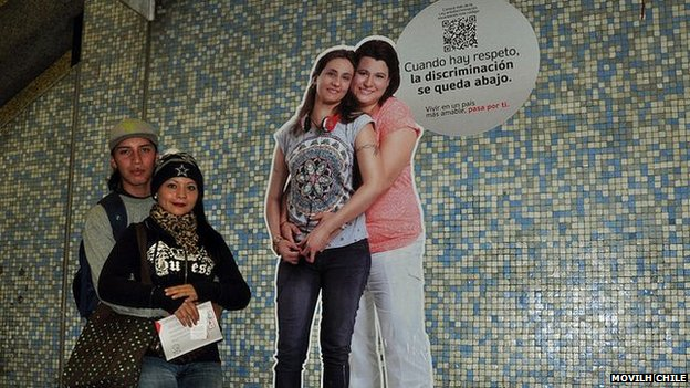 A couple pose in front of an advert promoting respect on the Santiago metro
