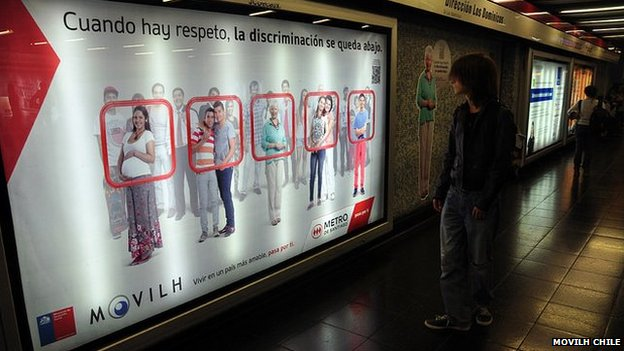 A man looks at an advert promoting respect on the Santiago metro
