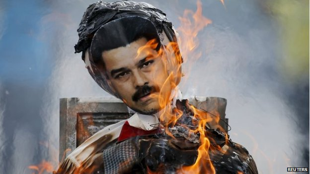 Anti-government protesters burn an effigy depicting Venezuela's President Nicolas Maduro in Caracas on 20 April , 2014