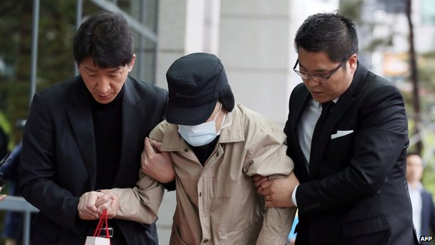 "Kim Han-Sik (C), the CEO of Chonghaejin Marine, the operator of the sunken ferry ""Sewol"", arrives at the prosecutors office in the western port city of Incheon on April 29, 2014. Prosecutors summoned on April 29 the head of the South Korean ship operator behind the sunken ferry, as part of widening investigations on the disaster that left 300 dead or missing"
