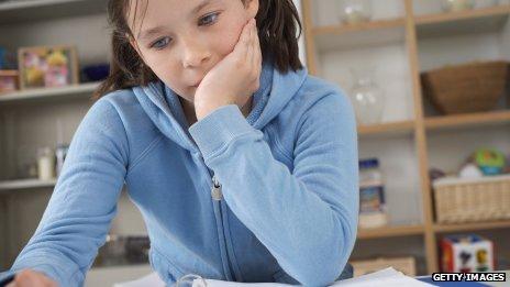 Girl does homework on a desk