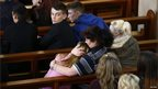 A child is comforted in Corpus Christi Catholic Church after teacher Ann Maguire was fatally stabbed at Corpus Christi Catholic College in Leeds