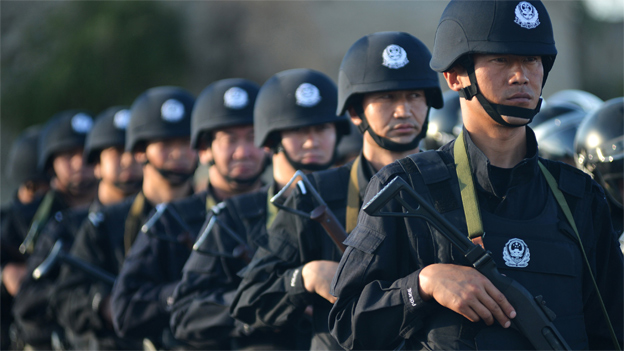 An anti-terrorism force including public security police and the armed police attend an anti-terrorism joint exercise in Hami, northwest China's Xinjiang region on July 2, 2013