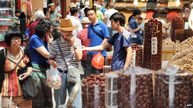 Tourists buy various local produce at the city bazaar in Urumqi, farwest China's Xinjiang region on July 5, 2013.