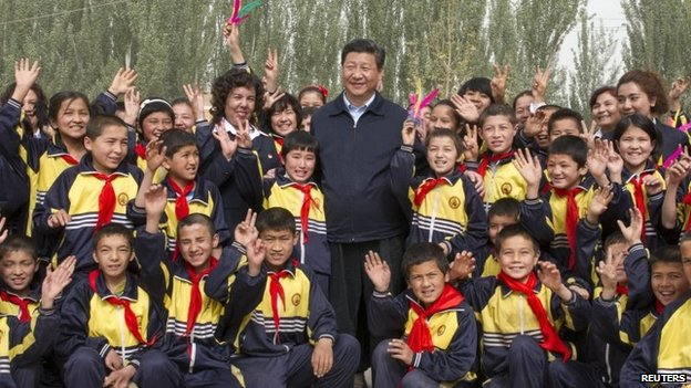 China's President Xi Jinping poses for pictures with primary school students in Shufu county, Xinjiang Uighur Autonomous region, in this picture taken 28 April 2014 by Xinhua News Agency and supplied to Reuters