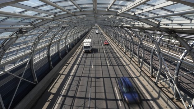 Cars drive through a soundproof tunnel covering a motorway in Warsaw, Poland. Photo: April 2014