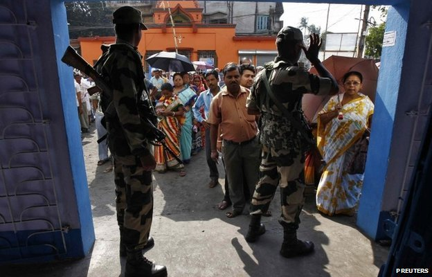 Paramilitary forces guard a polling station in India