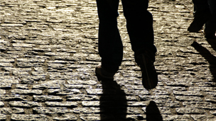 man walking on cobblestones