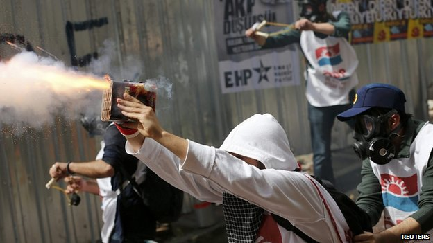 Demonstrators let off firecrackers at riot police during May Day protests 01/05/2014
