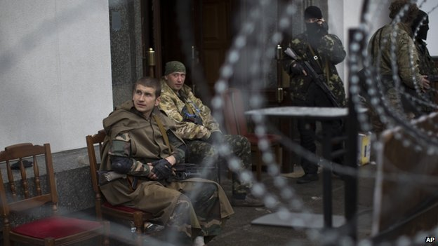 Pro-Russian gunmen guard an entrance to a government building in Luhansk, eastern Ukraine. Photo: 30 April 2014