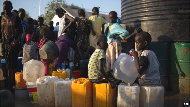 Children sit on jerry cans as they wait at a water distribution point at a camp for internally displaced people at the base of the United Nations Mission in South Sudan in Juba on 15 January 2014