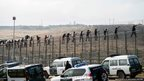 African migrants walk along a border fence covered in razor wire between Morocco and Spain's north African enclave of Melilla