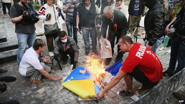 Pro-Russian activists burn a Ukrainian flag in Donetsk. Photo: 1 May 2014