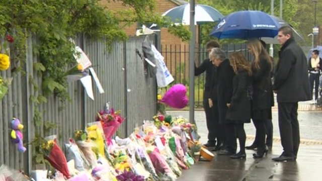 Ann Maguire's family inspect floral tributes
