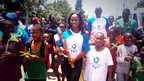 Female athlete holds the Queen's Baton, surrounded by smiling children waving Jamaican flags.