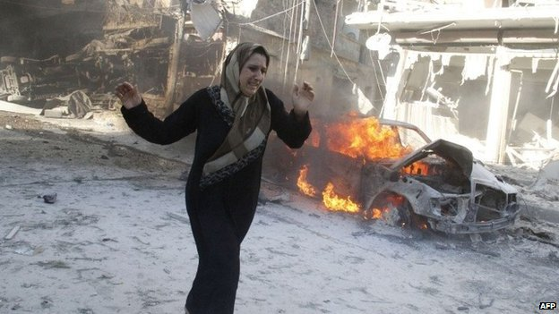 A woman walks past the burning wreckage of a car after an air strike in the Halak district of Aleppo (1 May 2014)