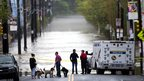 People gather to view the flood waters from the Schuylkill river along Main Street in Philadelphia, 1 May 2014