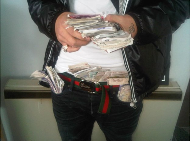 Man posing with cash in his trousers