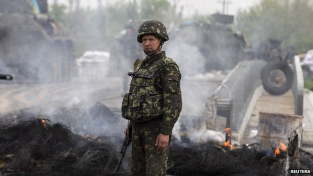 A Ukrainian solider stands near a destroyed rebel checkpoint near Sloviansk. Photo: 2 May 2014