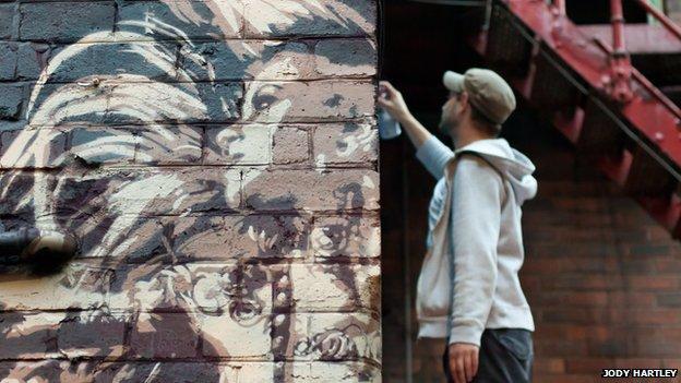 Artist sprays a wall at SFTOC 2013