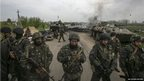 Ukrainian soldiers stand guard at a checkpoint near the eastern town of Slaviansk