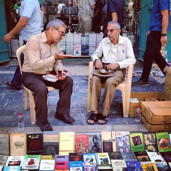 Two men discuss a book in Baghdad