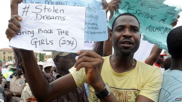 A man carries placard to campaign for the release of schoolgirls kidnapped by Boko Haram Islamists more than two weeks ago during worker's rally in Lagos on 1 May 2014
