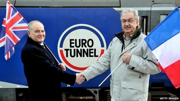 Former workers Philippe Cozette (R) and Graham Fagg, who dug the last metres of the tunnel pose in front of a train at the entrance of the tunnel, near Coquelles on 10 Feb 2014