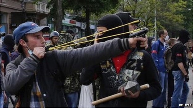 Pro-Russia militant with a catapult fires objects at pro-Kiev protesters in Odessa, 2 May 2014