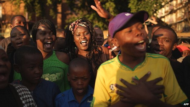 A large crowd of supporters sings the South African national anthem outside a hospital where former South African President Nelson Mandela was being treated in June 2013 in Pretoria, South Africa
