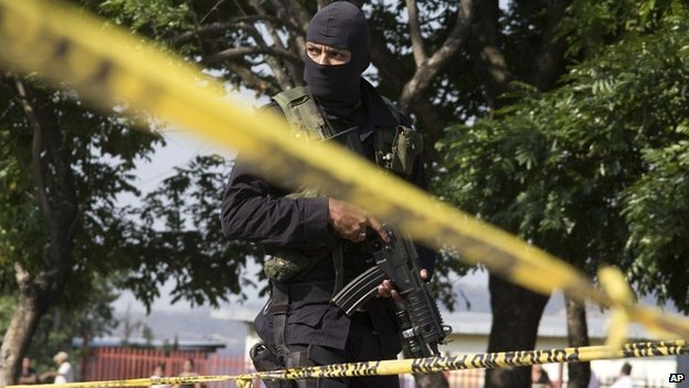 A police officer at the scene of a gang shooting in El Salvador - 13 April 2014