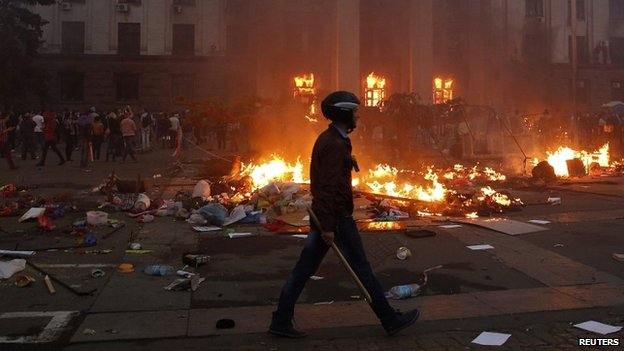 A protester walks past a burning tent camp and a fire in the trade union building in Odessa - 2 May 2014