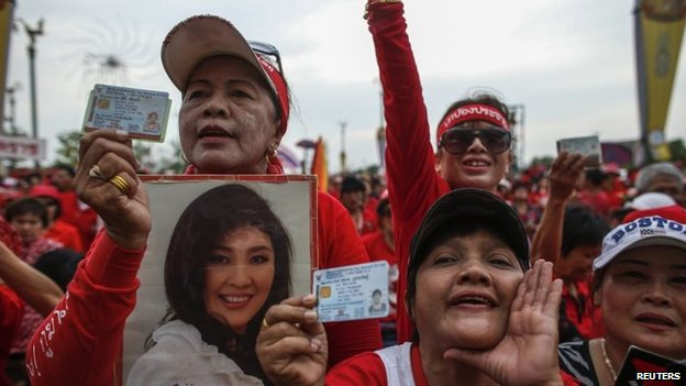 "File photo: A member of the pro-government ""red shirt"" group holds a picture of Thailand's Prime Minister Yingluck Shinawatra during a rally in Nakhon Pathom province on the outskirts of Bangkok, 5 April 2014"